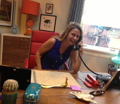 """Sitting at """"Mindy's"""" desk on set. I almost couldn't use this photo because it's embarrassing how big my smile is.... slightly excited to be there!"""